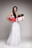 Smiling beautiful woman holding gifts. Young surprised woman holding multiple gifts. Beautiful elegant brunette carrying her presents Stock Images
