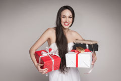 Smiling beautiful woman holding gifts. Young surprised woman holding multiple gifts. Beautiful elegant brunette carrying her presents Royalty Free Stock Photo