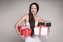 Smiling beautiful woman holding gifts. Young surprised woman holding multiple gifts. Beautiful elegant brunette carrying her presents Stock Photography