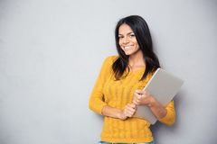 Smiling beautiful woman holding laptop Stock Photo
