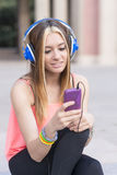 Smiling beautiful woman listening to music with headphones and p Royalty Free Stock Image
