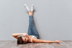 Smiling beautiful woman lying on the floor with raised legs Royalty Free Stock Images
