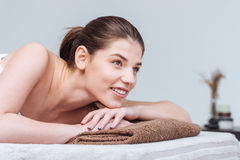 Smiling beautiful woman lying on massage table in spa salon Stock Photo