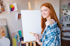Smiling beautiful woman painter making sketches on blank canvas. Smiling beautiful young woman painter with long red hair making sketches on blank canvas in Stock Photo