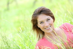 Smiling beautiful woman in pink t-shirt in grass Royalty Free Stock Photos