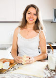 Smiling beautiful woman preparing cakes of dough Stock Photography