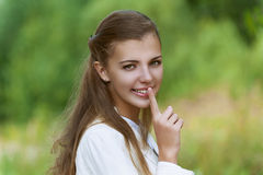 Smiling beautiful woman puts finger Royalty Free Stock Photo