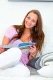 Smiling beautiful woman reading magazine on sofa Stock Photos