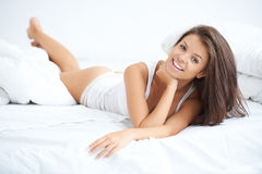 Smiling beautiful woman relaxing in bed Royalty Free Stock Photography