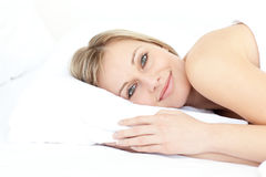 Smiling beautiful woman relaxing on her bed Royalty Free Stock Photography