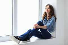 Smiling beautiful woman relaxing on window sill. Wellbeing concept Royalty Free Stock Photography