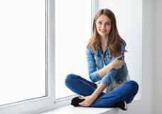 Smiling beautiful woman relaxing on window sill. Wellbeing concept Stock Photo