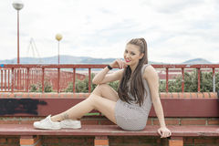 Smiling beautiful woman sitting on wood bench. Royalty Free Stock Photography