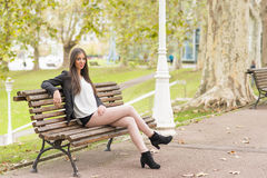 Smiling beautiful woman sitting on wood bench, outdoor. Stock Images
