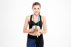 Smiling beautiful woman in sportswear standing with skipping rope Stock Photo