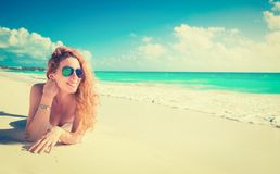 Smiling beautiful woman sunbathing on a beach. Happy smiling beautiful woman with sunglasses sunbathing on a beach Stock Images