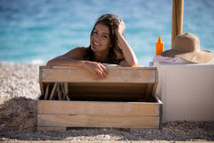 Smiling beautiful woman sunbathing in a bikini on a beach at tropical travel resort Royalty Free Stock Photography