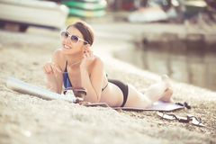 Smiling beautiful woman sunbathing in a bikini on a beach at tropical travel resort Royalty Free Stock Images