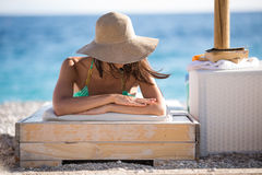 Smiling beautiful woman sunbathing in a bikini on a beach at tropical travel resort Royalty Free Stock Image