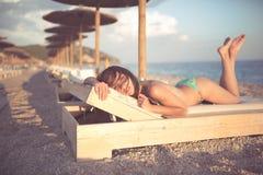 Smiling beautiful woman sunbathing in a bikini on a beach at tropical travel resort Stock Photo