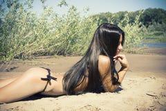 Smiling beautiful woman sunbathing topless on a beach Stock Photo