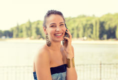 Smiling beautiful woman talking on mobile phone outdoors by the lake stock photography