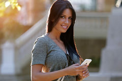 Smiling beautiful woman texting with her phone in the garden. Royalty Free Stock Image