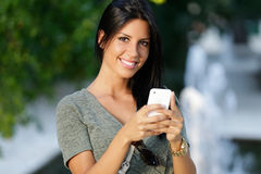 Smiling beautiful woman texting with her phone in the garden. Stock Photo