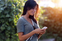 Smiling beautiful woman texting with her phone in the garden. Royalty Free Stock Photography