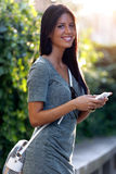 Smiling beautiful woman texting with her phone in the garden. Royalty Free Stock Photo