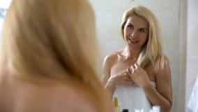 Smiling beautiful woman touching hair, shampoo for dyed weak hair, beautician. Stock photo royalty free stock photo