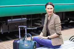 Smiling beautiful woman with travel bag and a suitcase. Smiling beautiful adult woman with travel bag and a suitcase against the backdrop of the railway carriage Royalty Free Stock Photo