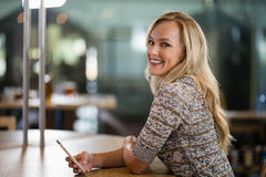 Smiling beautiful woman using mobile phone at bar counter Stock Photography