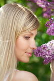 Smiling beautiful woman with violet flowers Royalty Free Stock Images