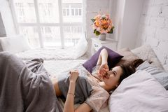 Smiling beautiful woman waking up in the morning. Thoughtfulness, calmness and relaxation, staying in bed for a while, good start of the day concept Stock Photos
