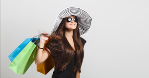 Smiling beautiful woman wearing hat and black sunglasses holding Stock Photos