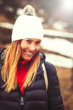 Smiling beautiful woman, winter clothes. A smiling woman with wool hat and jacket with goose down. Intense sunshine. Vacation in the mountains Stock Photography
