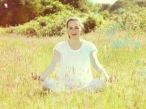 Smiling beautiful yoga girl cross-legged relaxing, summer romantic filter Stock Photo