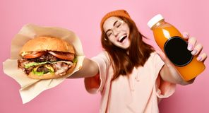Smiling beautiful young blond woman model in hipster hoodie cloth holding hamburger and bottle juice stock photo
