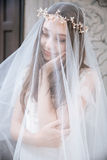 Smiling beautiful young bride in wreath covered with veil Stock Photos