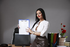 Smiling beautiful young brunette businesswoman showing blank not Royalty Free Stock Images