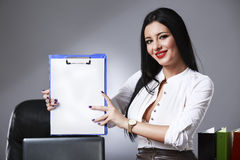 Smiling beautiful young brunette businesswoman showing blank not Stock Photo