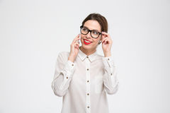 Smiling beautiful young business woman in glasses talking on smartphone Stock Images