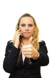 A smiling beautiful young business woman with a mobile phone pos. Ing with the thumbs up sign Stock Photo