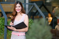 Smiling beautiful young business woman standing and holding fold. Ers at garden Royalty Free Stock Images