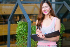 Smiling beautiful young business woman standing and holding fold. Ers at garden Stock Photography