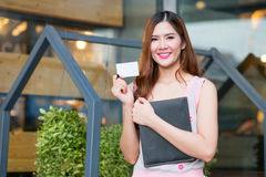 Smiling beautiful young business woman standing and holding fold. Ers ,showing blank name card Stock Image