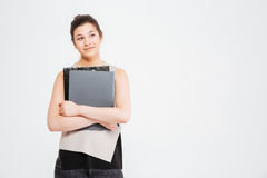 Smiling beautiful young business woman standing and holding folders Royalty Free Stock Photo