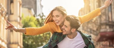 Smiling beautiful couple dating outdoors. Smiling beautiful young couple in love, on the city street, dating and having fun together royalty free stock images