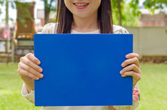 Smiling beautiful young girl holding a  communication board. Stock Photo